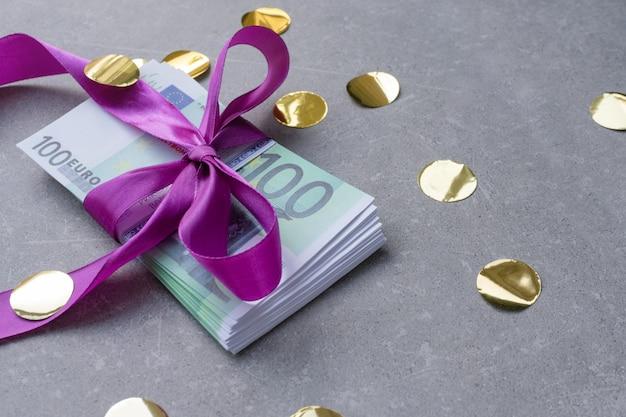 Honderd eurobankbiljetten op een stapel met violette strik.