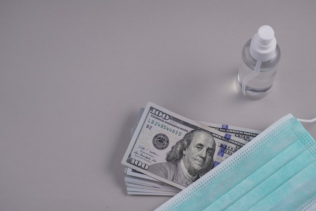 Honderden dollars stapelen zich op en een beschermingsmasker met een ontsmettingsfles