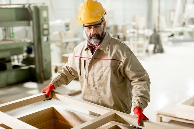 Honderdjarige arbeider van middelbare leeftijd die in de meubelfabriek werkt