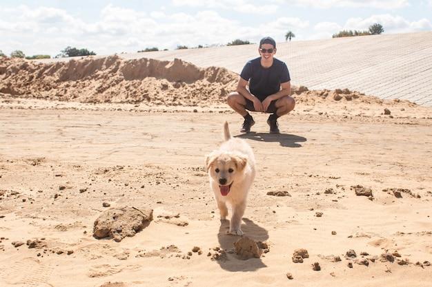 Hondje wandelen in het zand met zijn baasje.