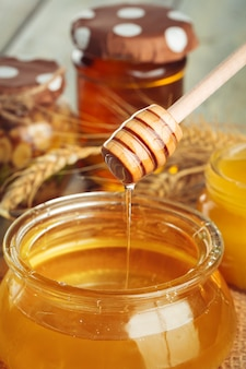 Honey achtergrond. zoete honing in glaskruik op houten achtergrond.