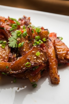 Honey chilli potato wedges, populair indiaas-chinees startersrecept, gegarneerd met sesam en ui. selectieve focus