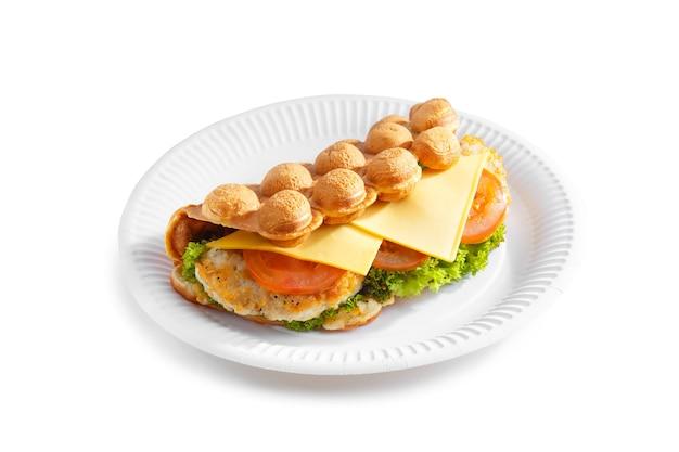 Hong kong bubbelwafels. bubble wafel met kaas, gebakken kip, tomaat en salade op papieren bord geïsoleerd op een witte achtergrond.