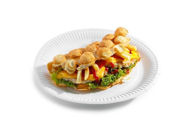 Hong kong bubble wafels bubble wafel met gebakken kip frietjes kaas tomaat en salade op papieren bord geïsoleerd op een witte achtergrond
