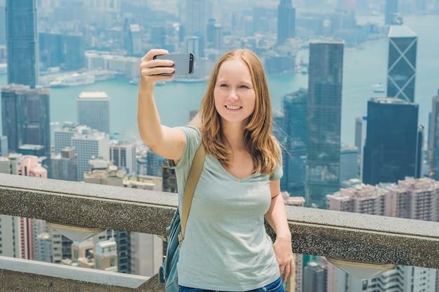 Hong kong victoria peak vrouw selfie stick foto foto met smartphone genieten van uitzicht over