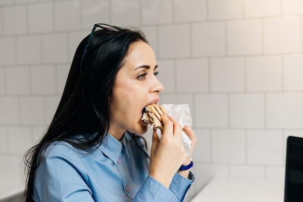 Hongerig jong meisje eet gretig een broodje in een café