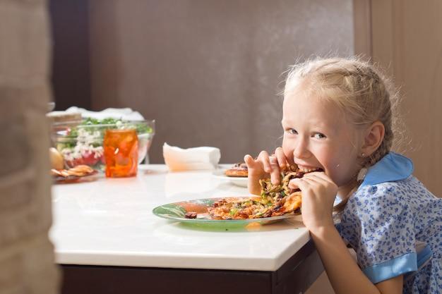 Hongerig mooi meisje verslindt zelfgemaakte pizza