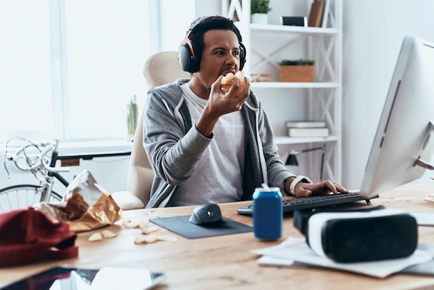 Hongerig voelen. geconcentreerde jonge man in vrijetijdskleding die computer gebruikt en chips eet terwijl hij thuis tijd doorbrengt