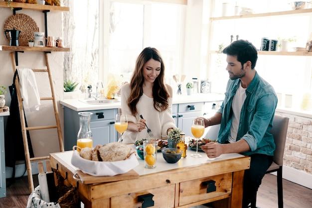 Hongerig voelen. mooi jong stel geniet van een gezond ontbijt terwijl ze thuis in de keuken zitten