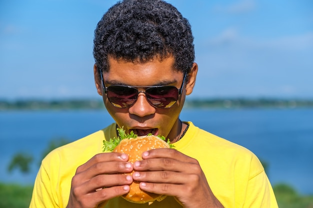 Hongerige afro-amerikaanse man geniet van de smaak van hamburger buiten in de zomer. concept van liefde voor junkfood dieet