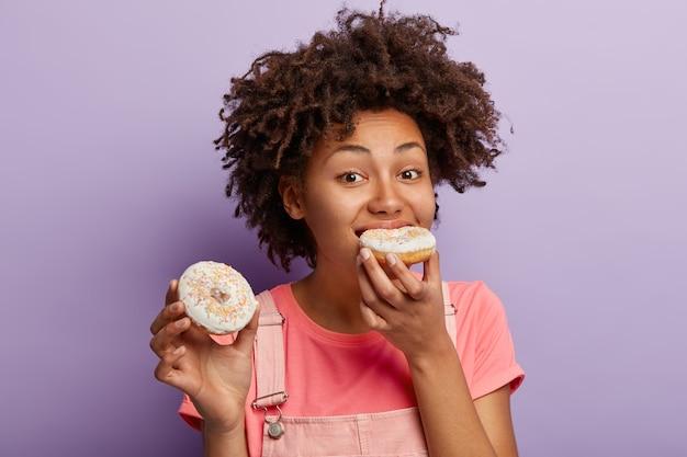 Hongerige afro-vrouw bijt smakelijke donut met heldere hagelslag, heeft ongezonde voeding, kan zich geen leven voorstellen zonder zoete desserts, heeft krullend kapsel, houdt zich niet aan een dieet, geïsoleerd op paarse muur