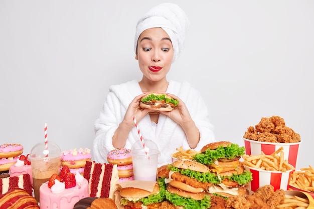 Hongerige aziatische vrouw likt roodgeverfde lippen en kijkt naar smakelijke hamburgers plukt heerlijk snackpauzedieet