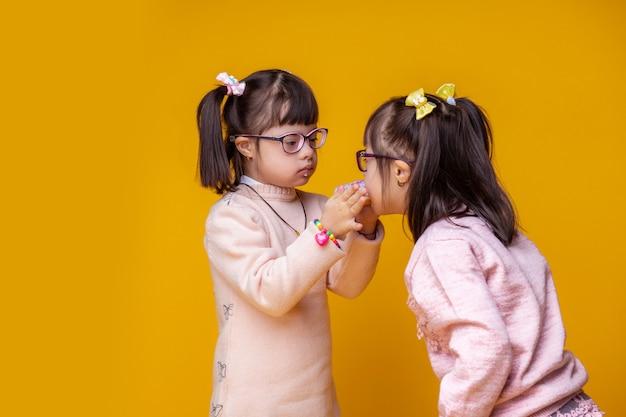 Hongerige dankbare zus. mooie kleine tweeling met een psychische stoornis die elkaar voeden met zoete, gezwollen donuts