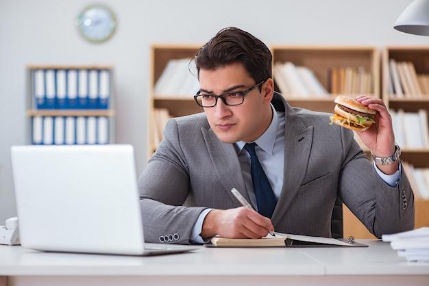 Hongerige grappige zakenman die ongezonde kostsandwich eet
