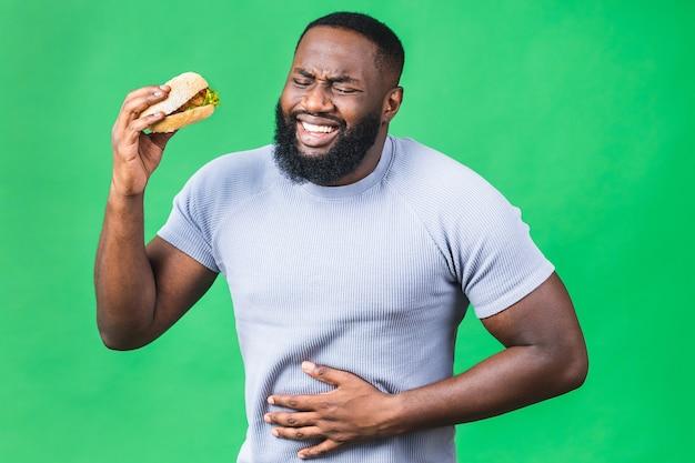 Hongerige jonge afro-amerikaanse zwarte man eten hamburger geïsoleerd op groene achtergrond. maagpijn.