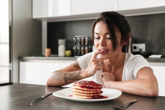 Hongerige jonge vrouwenzitting bij de keuken in huis