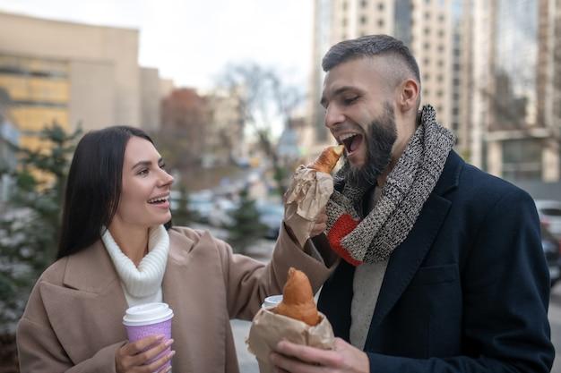 Hongerige jongeman die een heerlijke croissant bijt terwijl hij wordt gevoerd door zijn vrouw