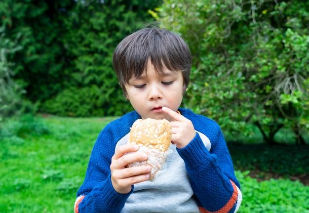 Hongerige jongen die eigengemaakte broodsandwiches met gemengde groenten in het park eet