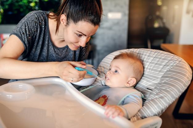 Hongerige kaukasische babyjongen met slab in zijn stoel zitten en het eten van babyvoeding. zijn moeder gaf hem voor het eerst eten.