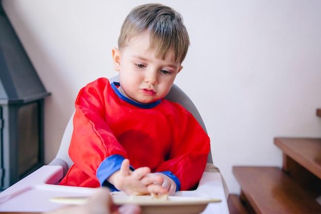 Hongerige kleine babyjongen die geen groenten wil eten. gedragsproblemen bij het eten van kleine kinderen.