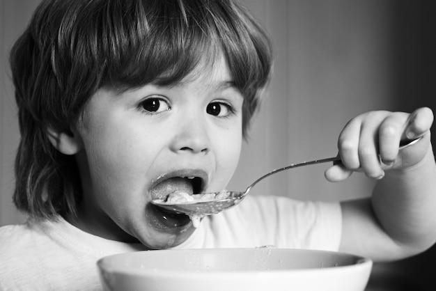 Hongerige kleine jongen die eet. vrolijk babykind eet zelf voedsel met een lepel. lekker kinderontbijt