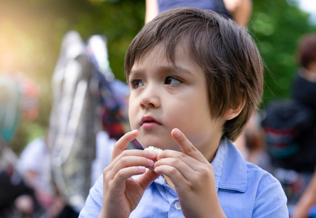 Hongerige kleine jongen die verse tortillaomslagen met kip eet