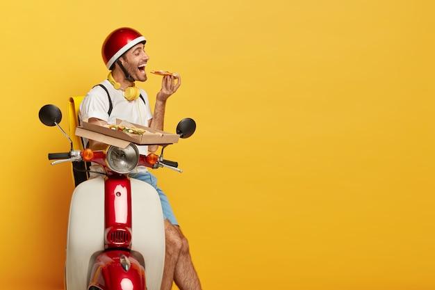 Hongerige knappe mannelijke bestuurder op autoped met rode helm die pizza levert