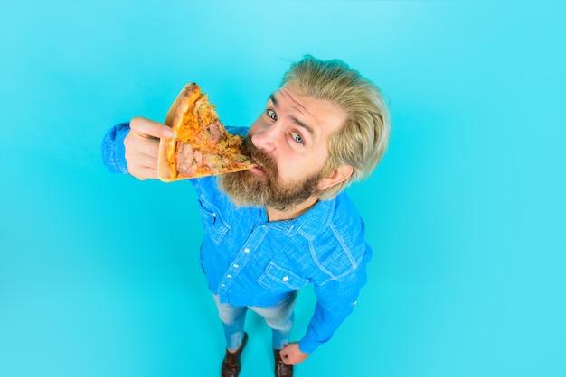 Hongerige man eet pizza fastfood pizzeria bebaarde man eet stuk pizza italiaanse keuken concept