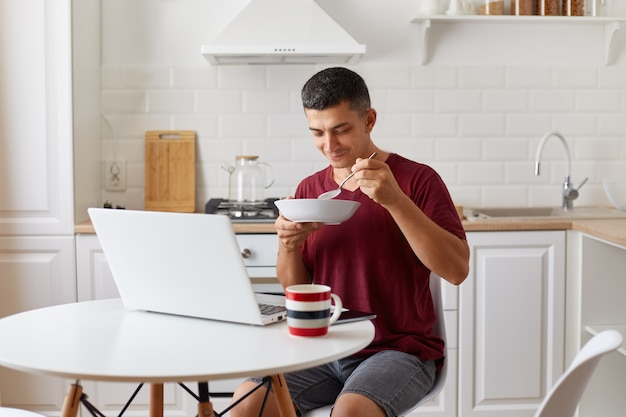 Hongerige man freelancer zittend in de keuken aan tafel voor opengeklapte laptopcomputer en soep eten, bord in handen houden, aantrekkelijke man met bordeaux casual stijl t-shirt.