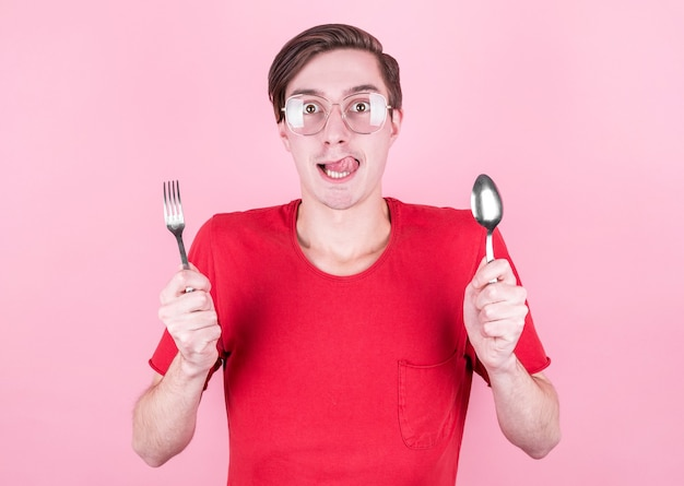 Hongerige man houdt een vork en lepel in zijn handen en denkt over heerlijk eten over roze muur. dieet en maaltijdconcept.