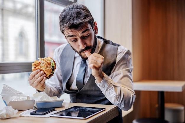 Hongerige man in pak zittend in fastfoodrestaurant op lunchpauze, kaas hamburger eten en nieuws lezen op tablet.