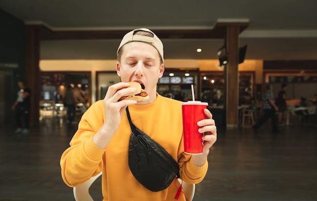 Hongerige man in straatkleding en pet zit in een café en eet een broodje met een glas cola in zijn hand.