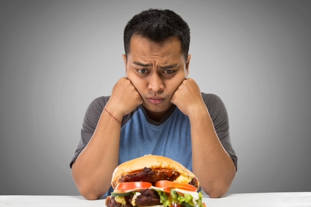 Hongerige mens die grote hamburger bekijkt