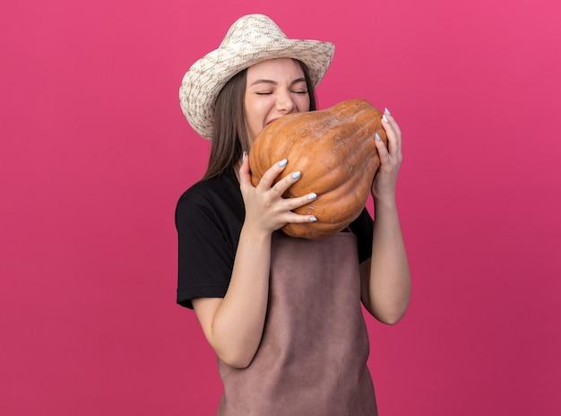 Hongerige, mooie blanke vrouwelijke tuinman met een tuinhoed die doet alsof hij pompoen bijt, geïsoleerd op een roze muur met kopieerruimte