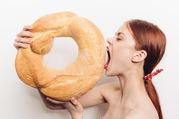 Hongerige roodharige vrouw die een groot brood op een licht eet.