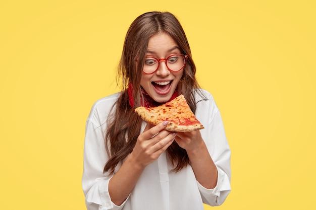 Hongerige student opent mond wijd terwijl hij een heerlijk stuk pizza ziet, wil eten, gekleed in wit overhemd, modellen tegen gele muur. positieve vrouw met ongezonde kost. mensen en eten