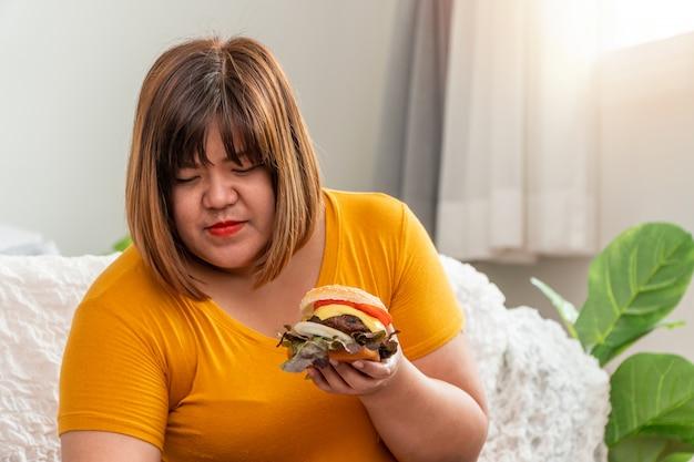 Hongerige te zware vrouw die en hamburger glimlacht houdt en in de slaapkamer zit, haar zeer gelukkig en geniet van fastfood te eten. concept van eetbuistoornis (bed).