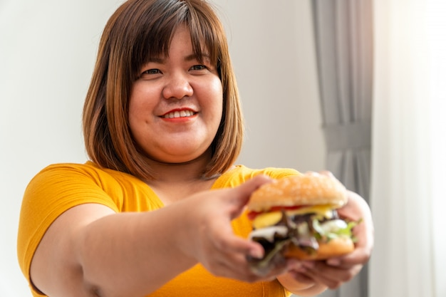 Hongerige te zware vrouw die en hamburger glimlacht houdt en in de slaapkamer zit