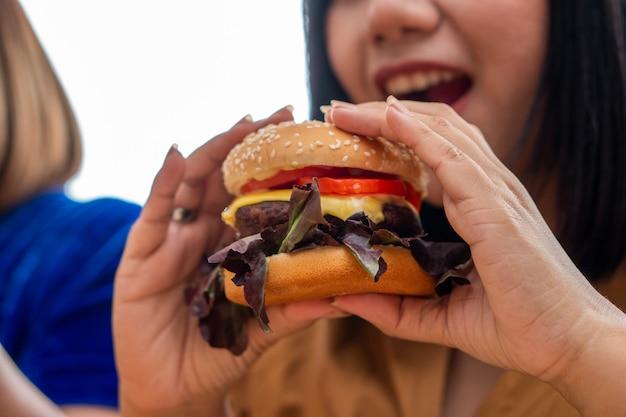 Hongerige te zware vrouw die en hamburger glimlacht houdt en in de woonkamer zit