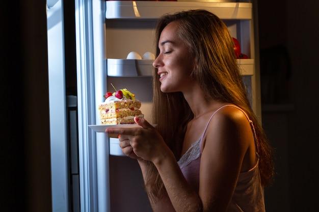 Hongerige vrouw die in pyjama zoete cake eet bij nacht dichtbij koelkast