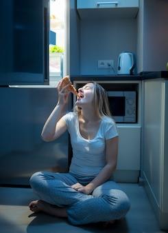 Hongerige vrouw die laat in de avond pizza eet op de keukenvloer