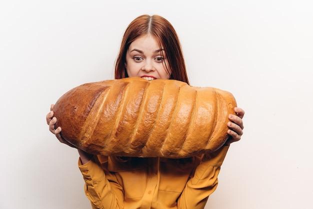 Hongerige vrouw met een enorm brood op een lichte achtergrond en een geel overhemd aan