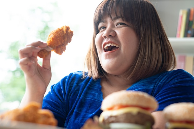Hongerige vrouw met overgewicht die fried chicken, hamburger op een houten bord en pizza op tafel vasthoudt, tijdens het werk vanuit huis, gewichtsprobleem krijgen. concept van eetbuistoornis (bed).