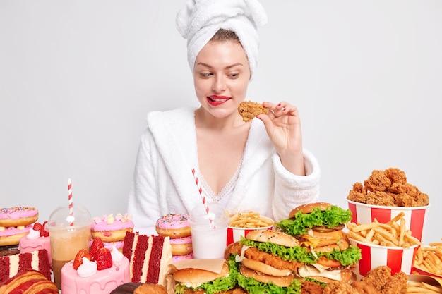 Hongerige vrouw met rode lippen kijkt naar een gebraden kippendrumstick