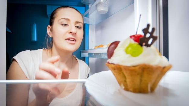 Hongerige vrouw op zoek naar iets om 's nachts in de keuken te eten. concept van een dieet en gezonde voeding.