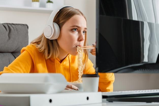 Hongerige vrouwelijke gamer eet noedels chinese schotel thuis interieur met behulp van desktop pc-computer tijdens een streaming video game vrouw tienermeisje hartstochtelijk werken programmering.