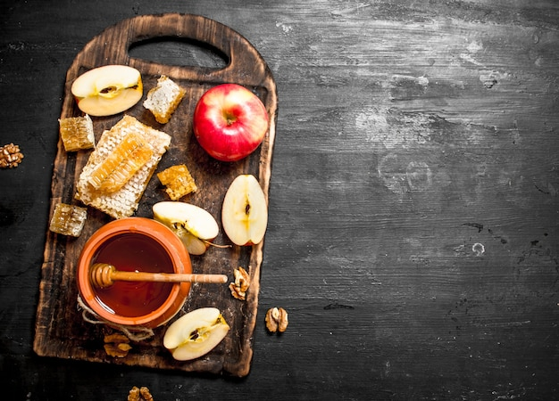 Honing achtergrond. honing in pot met plakjes rijpe appels en noten.