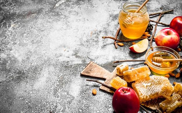 Honing achtergrond. honing met appels en noten op rustieke tafel.
