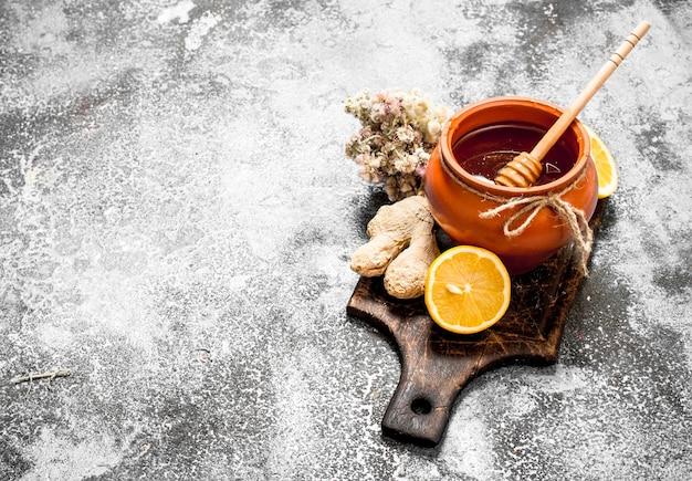 Honing achtergrond. honing met gember, citroen en kruiden. op rustieke achtergrond