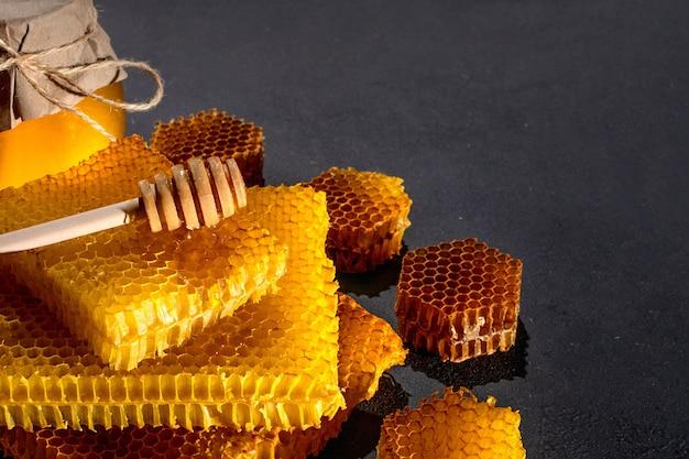 Honing achtergrond. natuurlijke honingraat en een houten lepel. op zwarte rustieke tafel.